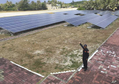 A member of the Taiwan coast guard shows the solar panels used for electrical power to visiting media on Taiping island, also known as Itu Aba, in the Spratly archipelago, roughly 1600 kms. (1000 miles) south of Taiwan, March 23, 2016.