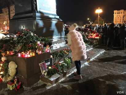 A woman approaches a memorial in Pushkin Square near the Kremlin, March 27, 2018, to those who died in a massive shopping mall blaze March 25 in the Siberian city of Kemerovo. A few hundred people were present at the vigil, though earlier there were ...