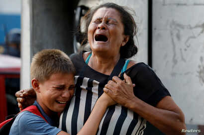 Relatives of inmates held at the General Command of the Carabobo Police react as they wait outside the prison, where a fire occurred in the cells area, according to local media, in Valencia, Venezuela March 28, 2018.