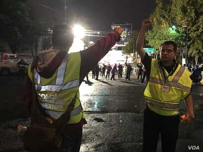 Volunteers working with the rescue teams in Mexico City signal to keep silent. The close fist is a sign to be quiet in order for the rescuers to listen and identify the location of survivors.