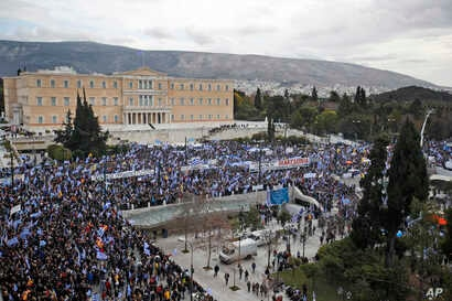 Protestors wave Greek flags outside parliament in Athens, Jan. 20, 2019. Greece's Parliament is to vote this coming week on whether to ratify the agreement that will rename its northern neighbor North Macedonia.
