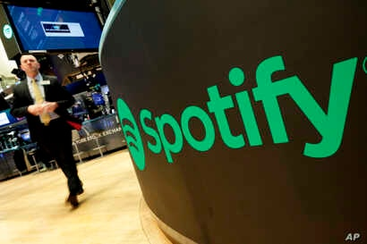 FILE - A trading post sports the Spotify logo on the floor of the New York Stock Exchange, April 3, 2018.