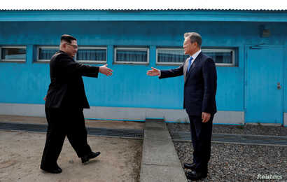 South Korean President Moon Jae-in and North Korean leader Kim Jong Un shake hands at the truce village of Panmunjom inside the demilitarized zone separating the two Koreas, South Korea.