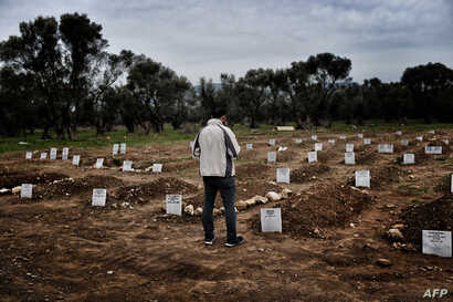 A man reflects while standing in front of graves in Mytilene on February 17, 2016, at a graveyard for refugees and migrants who drowned in their attempt to cross the Aegean sea from Turkey to the island of Lesbos.