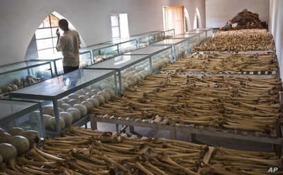 Mike Nkuzumuwami stands by the rows of human skulls and bones that form a memorial to those who died in the redbrick church that was the scene of a massacre during the 1994 genocide, and which he helps to look after, in the village of Nyarubuye, east...