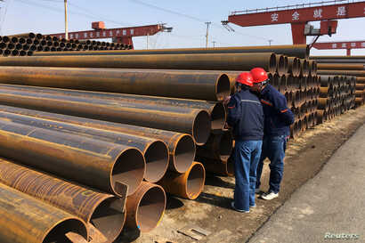 FILE - Workers inspect steel pipes at a steel mill of Hebei Huayang Steel Pipe Co Ltd in Cangzhou, Hebei province, China March 19, 2018.