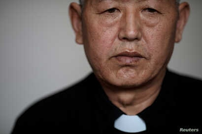 """Dong Guanhua, an outspoken priest and the head of a local """"underground"""" Catholic church, poses for a portrait in Youtong village, Hebei province, China, March 30, 2018."""