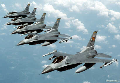 """FILE- Five U.S. Air Force F-16 """"Fighting Falcon"""" jets fly in echelon formation over the U.S. en route to an exercise in this undated file photograph."""