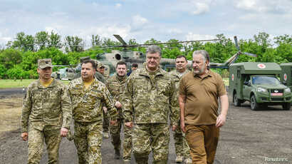 Ukrainian President Petro Poroshenko, second from right, in the front, meets with servicemen at a military mobile hospital during his visit to Donetsk region, Ukraine, June 14, 2017.