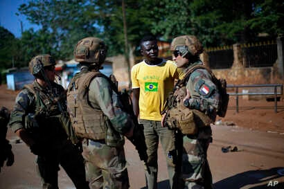 FILE - French Sangaris peacekeepers are seen speaking to a resident outside Fatima Church in Bangui, Central African Republic.