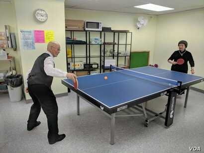Retired couple Ru-Liang Zhang, left, and Xan-Xia Hong play a game of ping pong at the New York Chinese Community Center, where they spend their weekday afternoons.