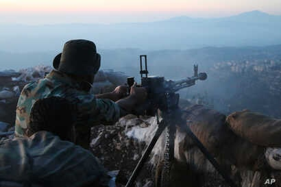 Syrian army personnel, backed by Russian airstrikes, fires machine gun in Latakia province, near border with Turkey, Oct. 10, 2015.