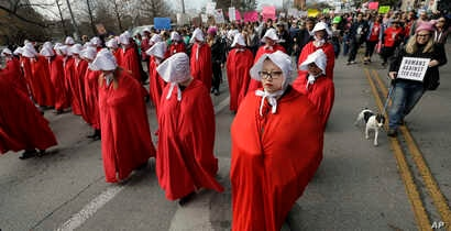 """Members of the """"Texas Handmaids"""" lead a women's march to the Texas State Capitol on the one-year anniversary of President Donald Trump's inauguration, Jan. 20, 2018, in Austin, Texas. The costumes are a nod to """"The Handmaid's Tale,"""" a novel and telev..."""
