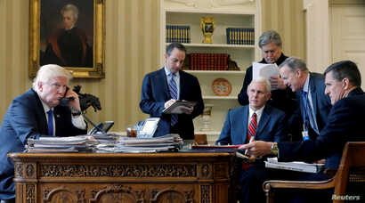 FILE - U.S. President Donald Trump (L-R), joined by Chief of Staff Reince Priebus, Vice President Mike Pence, senior advisor Steve Bannon, Communications Director Sean Spicer and National Security Advisor Michael Flynn, speaks by phone with Russia's ...