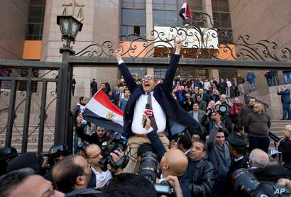 FILE - Khaled Ali, center, celebrates with other lawyers after winning a landmark case against the government, blocking its attempts to hand over control of two strategic Red Sea islands to Saudi Arabia, in Cairo, Egypt, Jan. 16, 2017. On Sept. 25, 2...