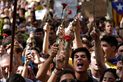 People gesture and wave flowers during a protest in Barcelona, Spain Thursday, Sept. 21, 2017.