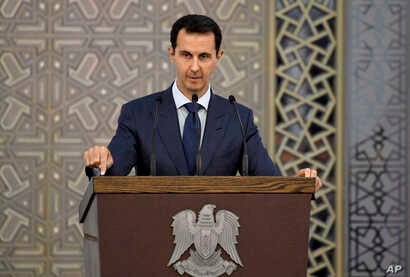 FILE - In a photo released by the official Facebook page of the Syrian Presidency, Syrian President Bashar al-Assad speaks to Syrian diplomats, in Damascus, Syria, Aug. 20, 2017.