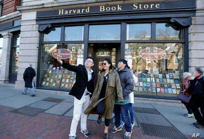 FILE - Students pose for a selfie outside the Harvard Book Store, March 9, 2017, in Cambridge, Mass. Readers have been flocking to classic works of dystopian fiction in the first months of Donald Trump's presidency.