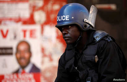 Police stand guard during a raid on the headquarters of  the opposition Movement for Democratic Change (MDC) a day after post-election clashes between security forces and opposition protesters in Harare, Zimbabwe, Aug. 2, 2018.