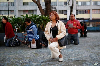 People kneel during a Mass held outside the Parish of Santiago Apostol, where church officials were waiting for inspectors to check damages following the recent earthquake, in the Plaza de las Tres Culturas in Tlatelolco, Mexico City, Sept. 24, 2017....