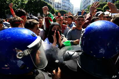 High school students face riot police officers as they protest in Algiers, Algeria, March 12, 2019.