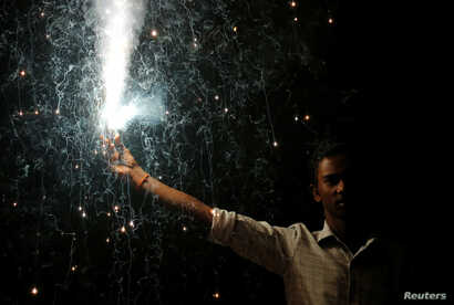 A man holds a firecracker while celebrating the Hindu festival of Diwali, the annual festival of lights in Mumbai, India,  Oct. 19, 2017.