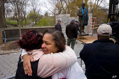FILE - Dr. Bernadith Russell hugs a friend as the statue of Dr. J. Marion Sims, is removed from New York's Central Park,  Apr. 7, 2018.