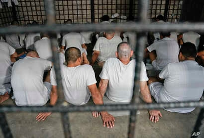Detainees sit on the floor during U.S. Attorney General Jeff Session tours a local police station and detention center in San Salvador, El Salvador, July 27, 2017.