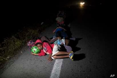 Jason, 11, sleeps using a toy ball as pillow during a break from walking early morning on the road that connects Pijijiapan with Arriaga, Mexico, Oct. 26, 2018. After a downpour, his family had tossed everything they had packed from home because the ...