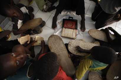 FILE - Koranic students memorize verses in the school where they live and study, in Dakar, Senegal, Aug. 31, 2010.