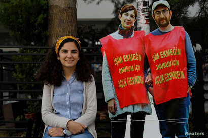 FILE - Esra Ozakca, wife of teacher Semih Ozakca, poses with cut-outs of her husband and fellow dissident, literature professor Nuriye Gulmen, during a protest against their detention, in Ankara, Turkey, June 16, 2017.