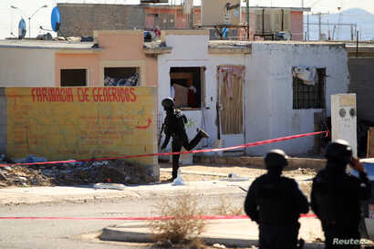 Policemen are seen at a crime scene following an attack on municipal police officers by drug hitmen, according to local media, in Ciudad Juarez, Mexico, Dec. 13, 2018.