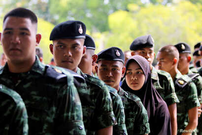 Soldiers and other people line up for their early vote for the upcoming Thai election at a polling station in Narathiwat province, Thailand, March 17, 2018.