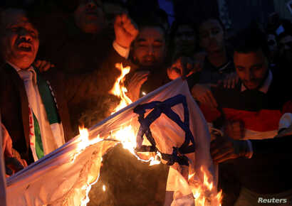 People shout slogans against Israel while burning a makeshift Israeli flag during a protest against U.S. President Donald Trump's Jerusalem declaration, in front of the Syndicate of Journalists in Cairo, Egypt, Dec. 7, 2017.