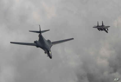 In this photo provided by S. Korea Defense Ministry, a U.S. Air Force B-1B bomber, left, flies with a South Korean fighter jet F-15K over the Korean Peninsula, South Korea,  July 30, 2017.