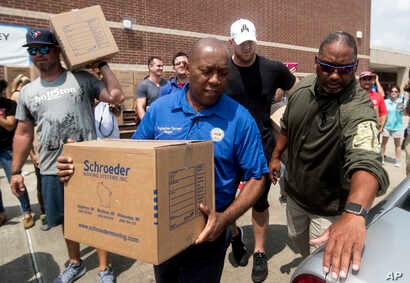 Houston Mayor Sylvester Turner, center, with Houston Texans Shane Lechler, left, and J.J. Watt, second right, distribute relief supplies to people impacted by Hurricane Harvey on Sunday, Sept. 3, 2017, in Houston.