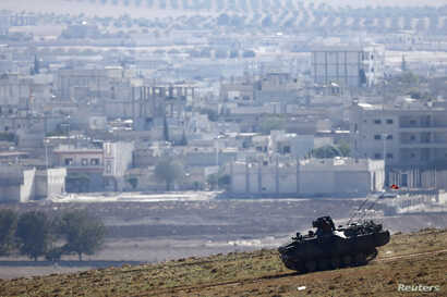 A Turkish army tank drives downhill, in front of ruins of the Syrian town of Kobani (seen in the background) near the Mursitpinar border crossing, on the Turkish-Syrian border, are seen in the background, near the southeastern town of Suruc in Sanliu...