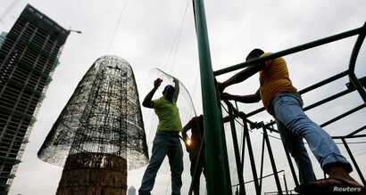 Construction workers work on a huge Christmas tree in an attempt to construct the world's tallest Christmas tree, in Colombo, Sri Lanka, Dec. 20, 2016.