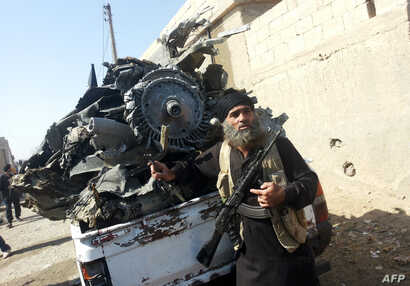 An armed jihadist stands next to the wreckage of a Syrian government forces aircraft which was shot down by militants of the Islamic State (IS) group over the Syrian town of Raqa on September 16, 2014. The plane crashed into a house in the Euphrates