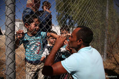 Ammar Hammasho from Syria, who lives in Cyprus, kisses his children who arrived at the refugee camp in Kokkinotrimithia outside Nicosia, Cyprus, Sept. 10, 2017.