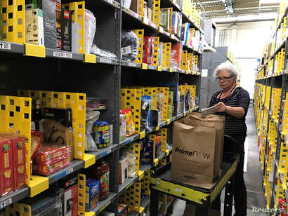 An employee collects items ordered by Amazon.com customers through the company's two-hour delivery service Prime Now in a warehouse in San Francisco, Calif., Dec. 20, 2017.