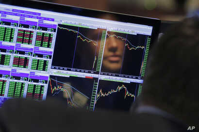 FILE- Specialist Frank Masiello is reflected in his screen on the floor of the New York Stock Exchange, Aug. 24, 2015.