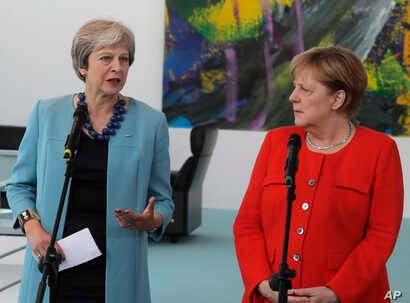 German Chancellor Angela Merkel, right, and British Prime Minister Theresa May give statements prior to a meeting in the chancellery in Berlin, Germany, July 5, 2018.