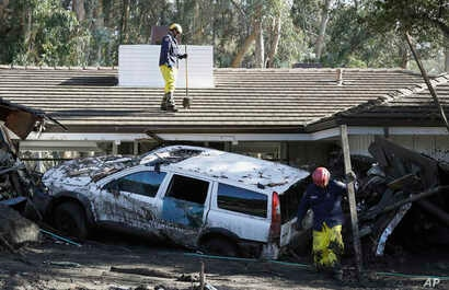Emergency crew members search an area damaged by storms in Montecito, Calif., Jan. 12, 2018.