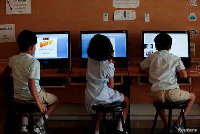 Students use computers in the technology lab at the Headstart private school in Islamabad, Pakistan, Oct. 9, 2017.