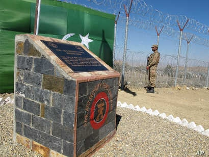 FILE - A Pakistani soldier stands guard at newly erected fence between Pakistan and Afghanistan at Angore Adda, Pakistan.