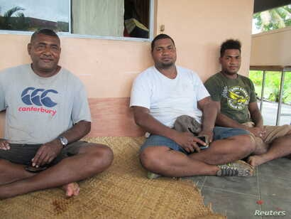 Rupeni Koto, who fled his home in Nasau, a village on Fiji's Koro island, after 2016's Cyclone Winston, sits on a porch with two of his sons, Soan, 25 (center) and Sekove, 21 (right), in the Fijian capital, Suva, Feb. 8, 2018.