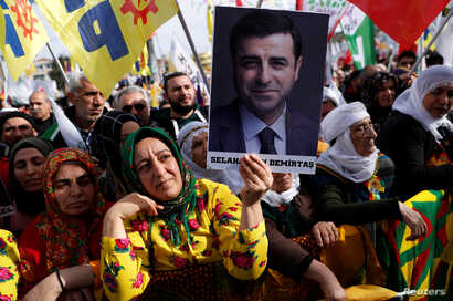 A demonstrator holds a picture of Selahattin Demirtas, jailed former leader of pro-Kurdish Peoples' Democratic Party (HDP), during a rally in Istanbul, Turkey, Feb. 3, 2019.