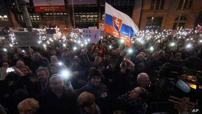 In this March 9, 2018 photo, demonstrators hold up their smartphones during an anti-government rally in Bratislava, Slovakia.