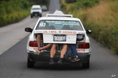 Central American migrants, part of the caravan hoping to reach the U.S. border, a ride on in the trunk of a taxi, in Acayucan, Veracruz state, Mexico, Nov. 3, 2018.